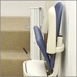 Electric stair lift with linked footrest and seat to prevent the need to bend and raise the footrest.