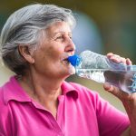 Senior woman drinking water outside