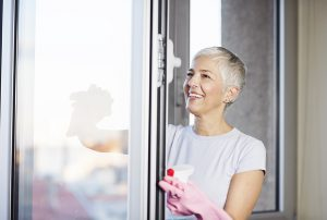 Senior woman cleaning easy to open window