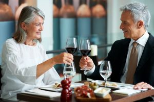 Happy senior couple having dinner at a restaurant and toasting with red wine
