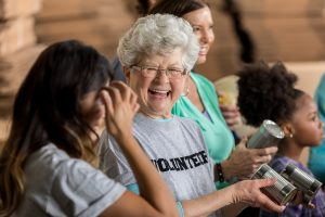 Cheerful senior Caucasian woman smiles and laughs with a young woman while volunteering at a food bank. They women are packing and organizing canned goods. She is wearing a gray volunteer t-shirt.