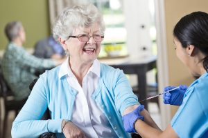 Nurse prepares to give senior patient a flu shot.