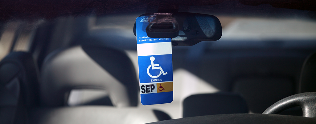 Disabled parking permit hanging in the window of a car.