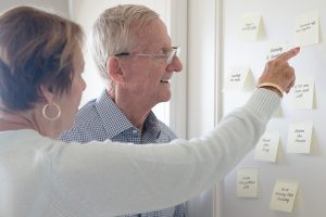 Elderly couple pointing and looking at sticky notes reminders