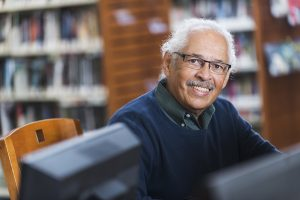Senior man using computer at library