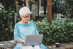 Senior woman blogging while sitting in her garden