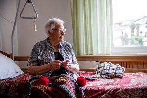 Senior lady crocheting in her room in retire community