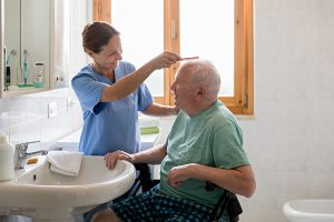 Nursing home combing patient hair