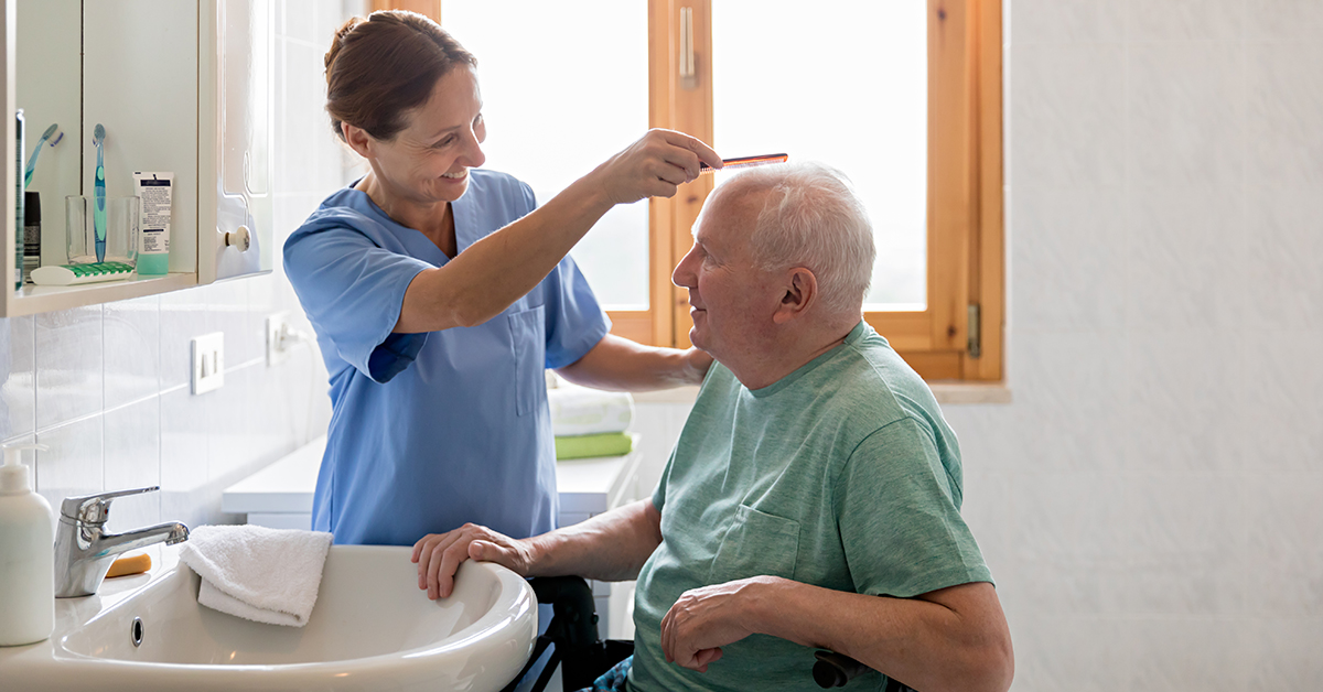 Senior assisted Living caregiver combing senior mans hair