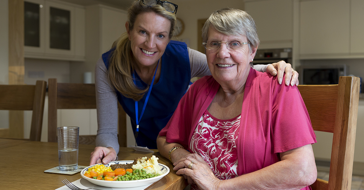 Caregiver feeding linch to elderly patient - Hire a caregiver for your elderly parent