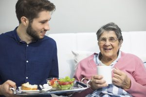 Caregiver bringing meal to senior patient - cost of hiring a caregiver