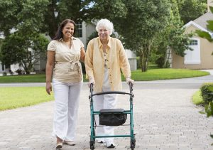 Caregiver helping senior take a walk