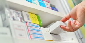 Pharmacist pulling medication from shelf