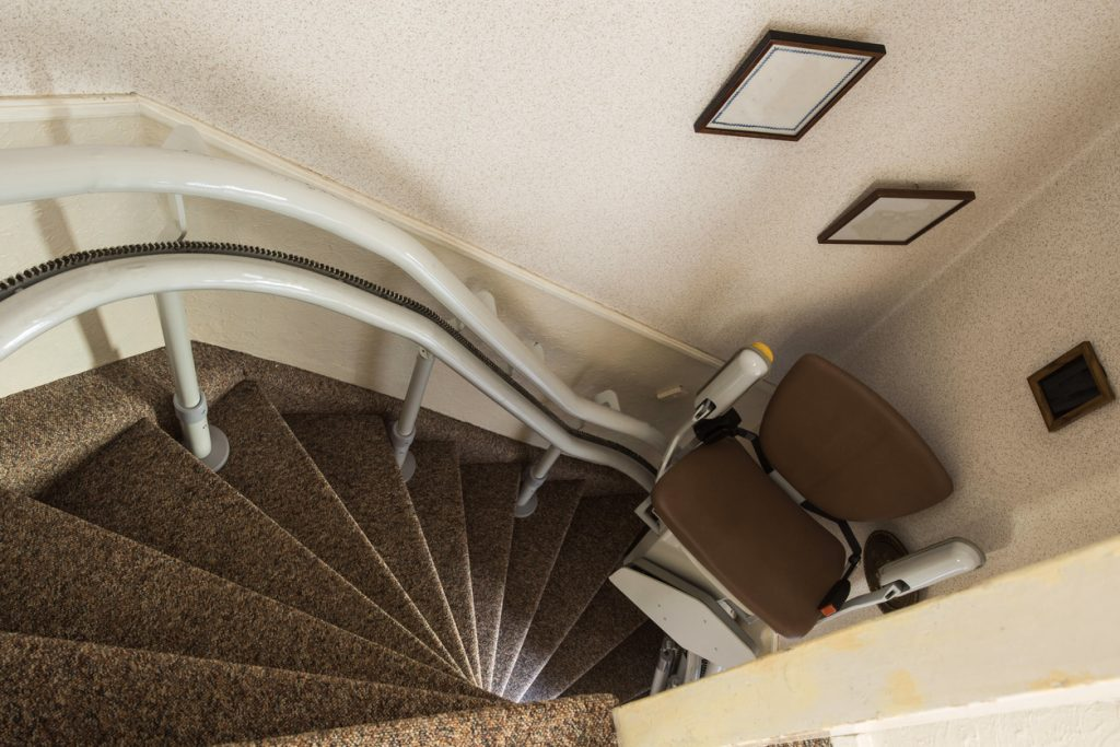 An empty stair lift at the bottom of a staircase