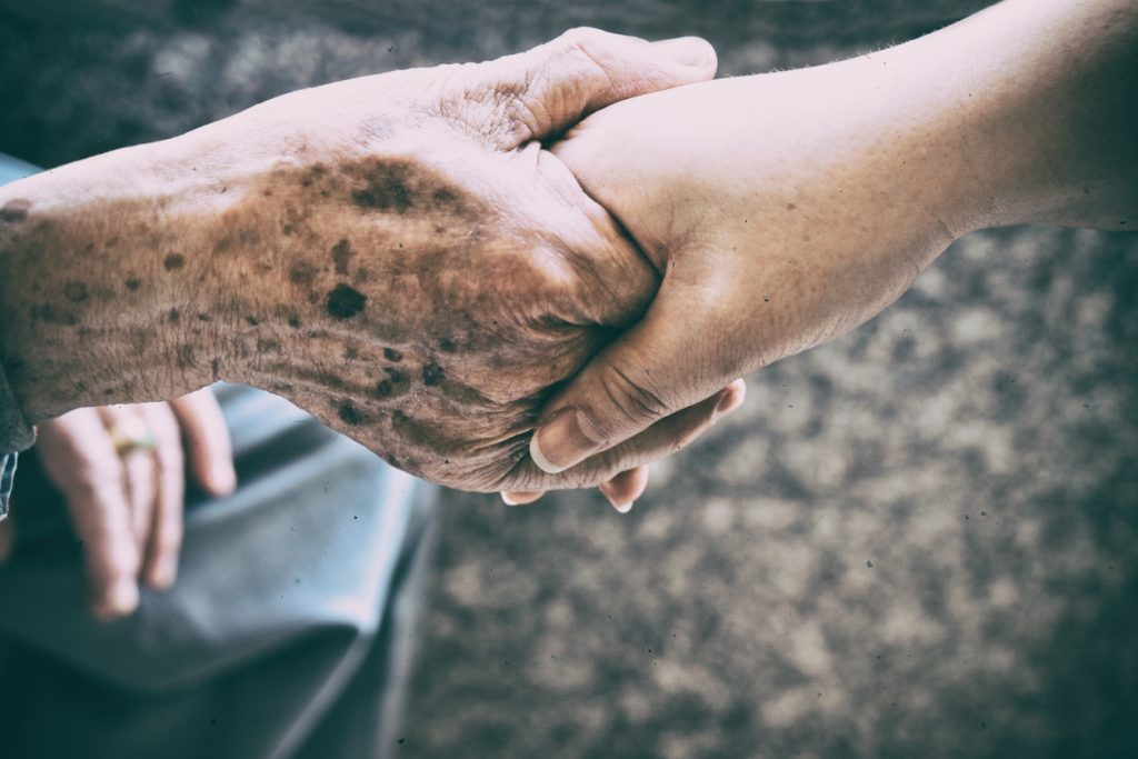 An elderly person with a younger caregiver