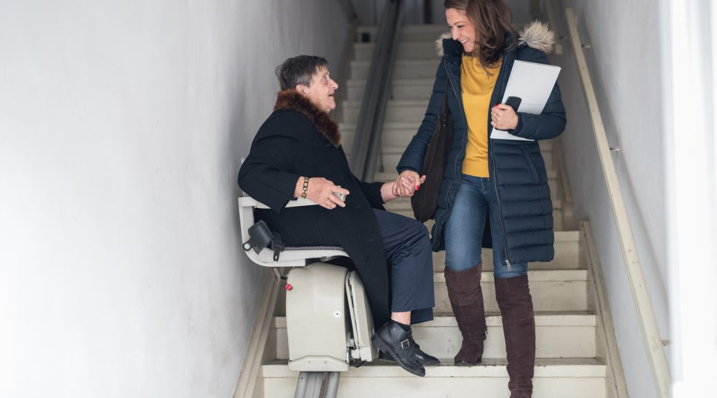 young woman helping older woman on stair lift