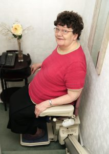 woman ascending stairs using stair lift