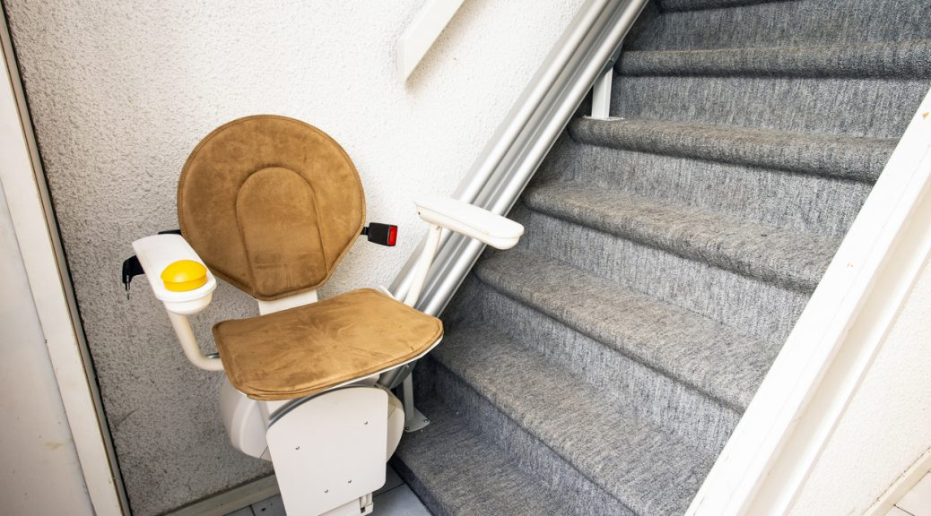 Automatic stair lift on staircase taking elderly people and disabled persons up and down in a house